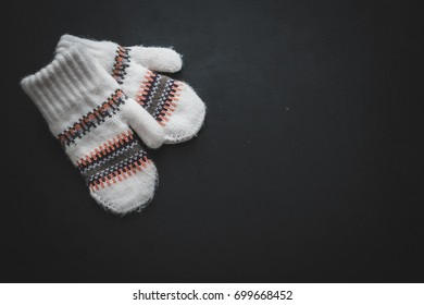 Christmas decorations. White knitted mittens with a winter pattern of snowflakes on a black background
