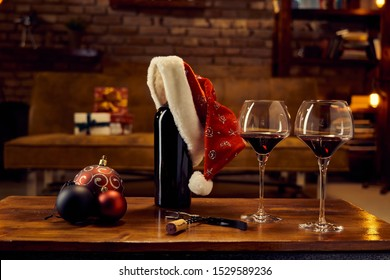Christmas decorations and wine glasses and a bottle of red wine on table at home dark living room in background. Winter mood with dark and warm colors.