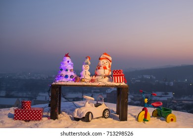 Christmas decorations, winter holidays, festive holiday or new year, party or corporate on the air outside the city, winter concept. Christmas tree toys, snow and gifts from Santa Claus