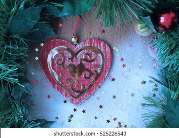 Christmas decorations. Wood red heart and glitter stars confetti.