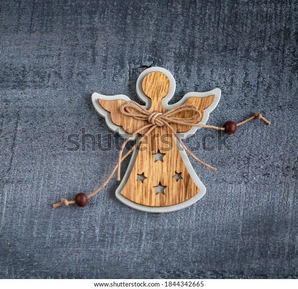 Christmas decorations wooden angel on wooden background close up