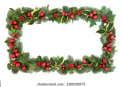 Christmas decorative background border with red bauble decorations, holly, fir, mistletoe and ivy isolated on white background. Festive theme.