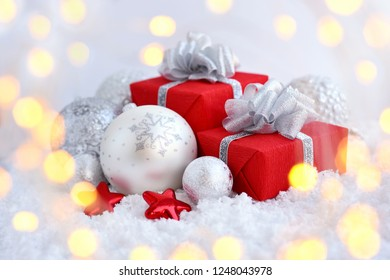 Christmas decorative balls and gifts on snow. Festive New Year background