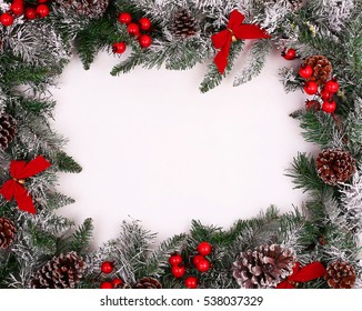 Christmas decorative border with pine cones and holly over white