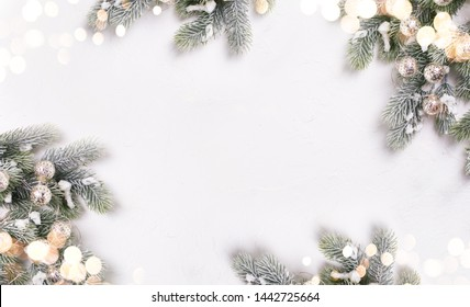 Christmas decorative branches fir tree and fairy lights on  white textured  background.  Selective focus. Place for text. View from above. Flat lay.