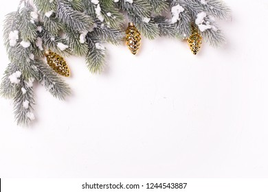 Christmas decorative gold pine cones and branches fur tree on  white textured  background. Decorative christmas composition. Selective focus. Place for text. View from above.