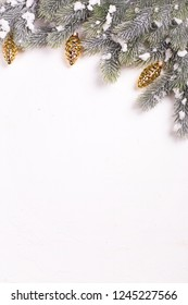 Christmas decorative gold pine cones and branches fur tree on  white textured  background. Decorative christmas composition. Selective focus. Place for text. View from above. Vertical image.