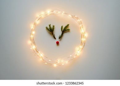 Christmas deer from tree branches and berry on whiteboard with lights