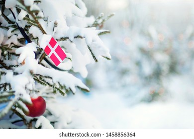 Christmas Denmark. Xmas tree covered with snow, decorations and a flag of Denmark. Snowy forest background in winter. Christmas greeting card.