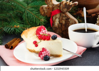 Christmas dessert. Homemade cheesecake with fresh frozen berries on christmas decor background.
