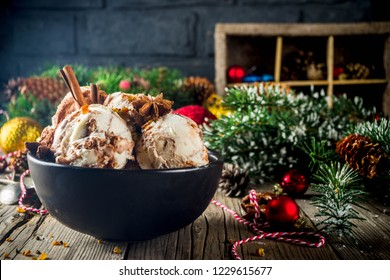 Christmas dessert, Homemade Eggnog or Gingerbread Ice Cream with Cinnamon, anise, spices, old wooden background with xmas decorations, copy space