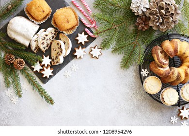 Christmas dessert table with traditional cake stollen, sweets and festive decoration. Overhead view