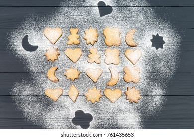 Christmas different shaped cookies with sugar powder on dark wooden table. Top view