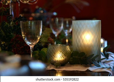 Christmas dining table fully dressed with decorations and foliage.