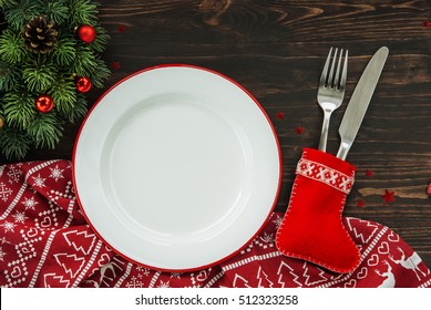 Christmas dinner background, plate, fork, knife and festive decoration on dark rustic wooden table, top view