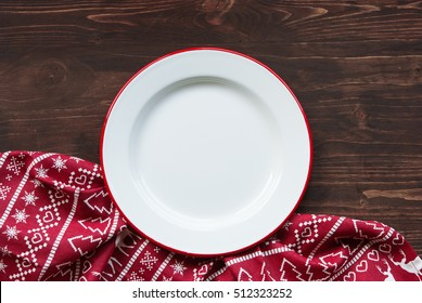 Christmas dinner background, plate and napkin on dark rustic wooden table, top view