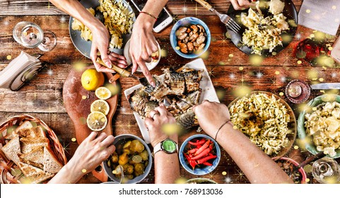 Christmas dinner. Falling golden snowflakes. Cheers! Top of view of a nicely served wooden table Christmas dinner with tasty dishes and snacks, friends are toasting with glasses of red and white wine