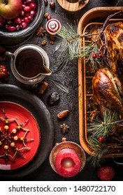 Christmas dinner. Festive table setting with roasted turkey served with pine branches and sauce on rustic background with burning candles, red plate, snowflakes decoration, fresh cranberries and apple