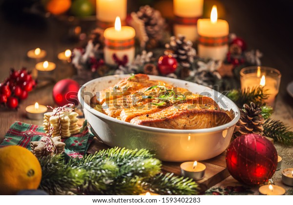 Christmas dinner from fish salmon in roasting dish with festive decoration advent wreath and burning candles .