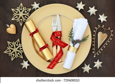 Christmas dinner place setting with gold plate, cutlery with red ribbon, napkin with ring and cedar sprig, cracker and gold bauble decorations on oak wood background