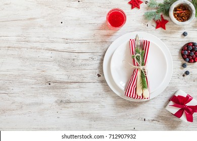Christmas dinner table served with empty plate with fork, knife and glass with compote on white wooden background. Top view. Spice, pepper, berries and furry spruce on a table.