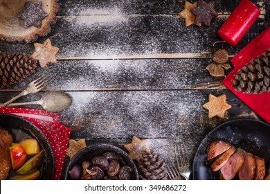 Christmas dinner table served with roasted duck breast, baked apples, chestnuts, gingerbread cookies. Decorated with candles, pine cones, snow. Christmas background with space for text. Xmas concept