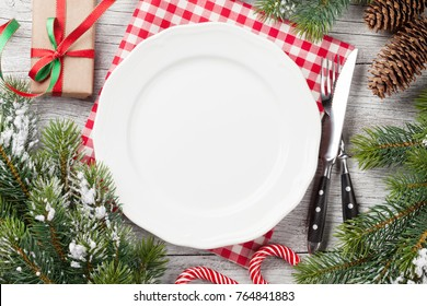 Christmas dinner table setting with fir tree, gift box. Top view with copy space