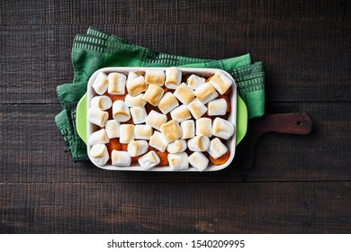 Christmas dish candied yams casserole with marshmallow topping, on a wooden cutting board with a green kitchen dish towel on a wooden table, copy space, horizontal, close-up