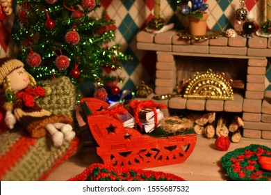 Christmas in dollhouse. Toy fireplace with decor. Handmade dollhouse for daughter. New Year's interior in miniature toy room. Cozy room for little toy doll. Handmade miniature winter accessories.