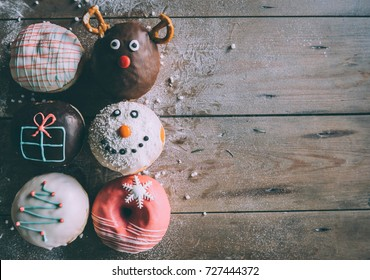 Christmas donuts served on wooden background with blank space