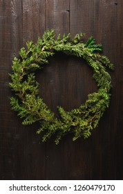 Christmas door wreath made of green tree fir branches and light garlands on dark brown wooden background table or door with red and golden Christmas baubles ornaments, copy space in center frame