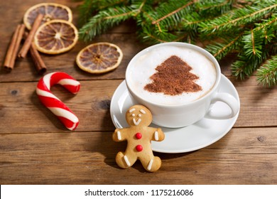 Christmas drink. Cup of cappuccino coffee with christmas tree drawing and gingerbread cookie, top view