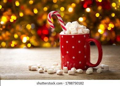 Christmas drink. Cup of hot chocolate with marshmallows and  red candy cane on festive background