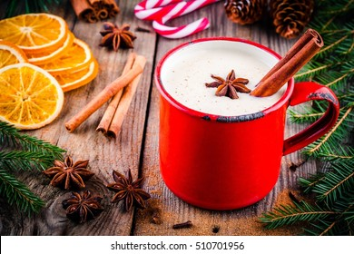 Christmas drink: eggnog with cinnamon and anise in red mug on wooden rustic background