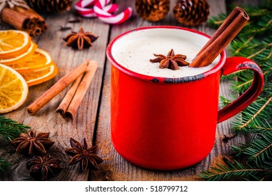 Christmas drink: hot white chocolate with cinnamon and star anise in red mug on wooden rustic background