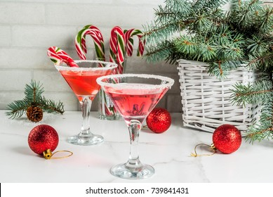 Christmas drinks, pink peppermint martini cocktail with xmas decoration and candy cane sweet on white marble kitchen table, copy space