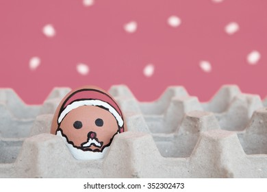 Christmas egg with faces drawn arranged in carton on snow background
