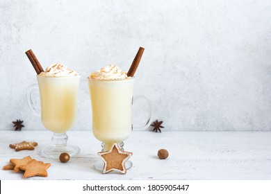 Christmas Eggnog drink with festive decor, gingerbread cookies and winter spices on white, copy space. Homemade eggnog for Christmas and winter holidays.