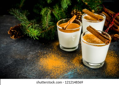 Christmas eggnog liqueur drink or cola de mono cocktail. traditional winter cocktail in short glasses, with xmas decorations, dark background copy space