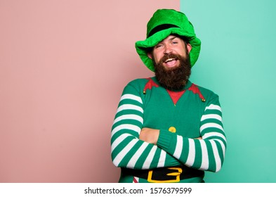 Christmas elf. Elf concept. Traditions or customs. Happy celebration. Bearded elf. Winter carnival. St Patricks day. Hipster with beard wearing green costume for party. Cheerful man celebrate holiday.