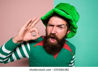 christmas elf. happy celebration. cheerful man with beard have fun. ireland beer tradition. Winter carnival. irish pub party. st patricks day. happy bearded hipster in green hat. ok gesture.