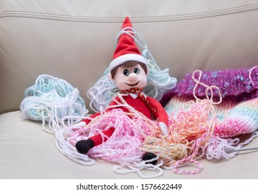 Christmas Elf mischief, naughty elf makes mess with knitting wool. Typical bad behaviour from toy elf