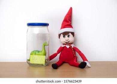Christmas Elf mischief, elf puts toy dinosaur in a jar.
