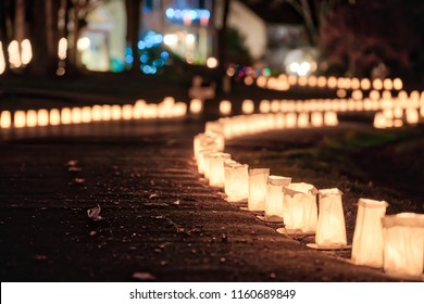 Christmas Eve candle lights, lanterns in paper bags at night along road, street, path illuminated by houses in residential neighborhood in Virginia