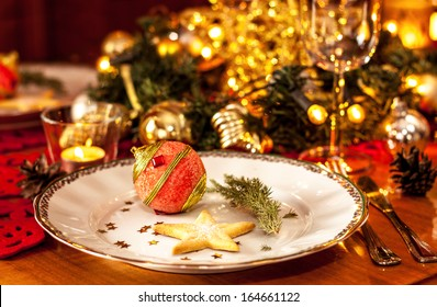 Christmas eve dinner party table setting with lights and gold glittering decorations - elegant white plate close up