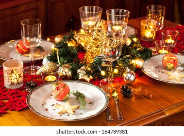 Christmas eve dinner party table setting with lights, gold glittering decorations and elegant white plates