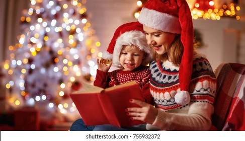 Christmas Eve. family mother and baby reading magic book at home near the fireplace and the Christmas tree