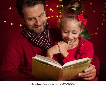 Christmas eve - happy family time. Smiling father and daughter read book on dark red background with lights.