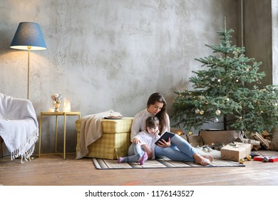 Christmas Eve. Mother and her daughter by the Christmas tree