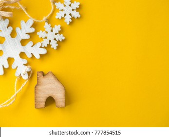 Christmas eve and new year ideas concept. Minimalist composition with wooden house and  white Christmas snowflake on bright yellow paper background with free copy space. Flat lay and selective focus